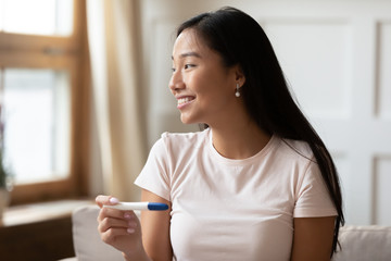 Happy Asian woman get positive ovulation test results