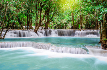 Travel to the beautiful waterfall in tropical rain forest, soft water of the stream in the natural park at Kanchanaburi, Thailand.