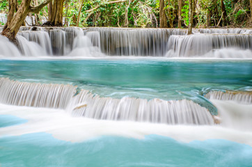 Zelfklevend Fotobehang Bos rivier Travel to the beautiful waterfall in tropical rain forest, soft water of the stream in the natural park at Kanchanaburi, Thailand.