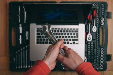 computer maintenance repair concept of man technician holding chrome socket wrench spanner on background with silver laptop on auto toolbox kit in workshop