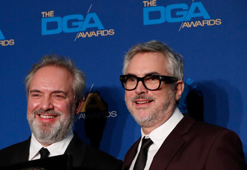 """Sam Mendes, director of """"1917"""", poses with presenter Alfonso Cuaron, while holding his winning medallion for Outstanding Directorial Achievement in Theatrical Feature Film category at the 72nd Annual Directors Guild Awards in Los Angeles,"""