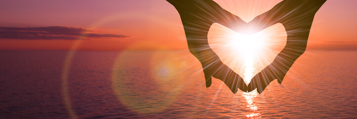 Two hands in the shape of a heart on a sunset background over the sea. The concept of a romantic date, a declaration of love, a love relationship.