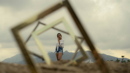 Young Woman Looking Away Seen Through Picture Frames Standing Against Sky During Sunset