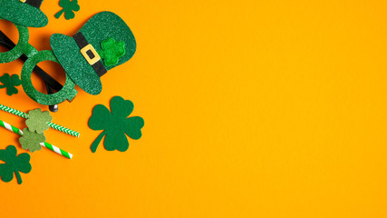 St Patricks Day banner with shamrock leaf clovers, Saint Patrick's Day party glasses and drinking straws on orange background. Flat lay, top view, copy space. Happy St Patrick's Day concept Wall mural