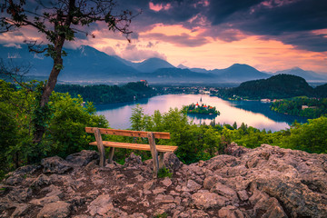 Wall Mural - Wooden bench and beautiful view with lake Bled at sunset