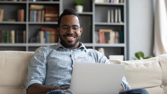 Smiling african man using laptop watching movies sit on sofa
