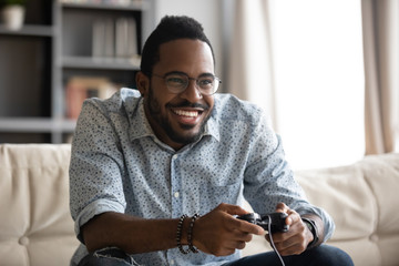 Happy young african guy holding joystick controller playing video game