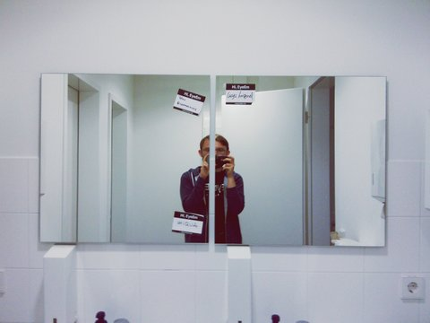 Young man clicking himself with camera phone at the mirror
