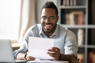 Cheerful african american male entrepreneur read great news in letter
