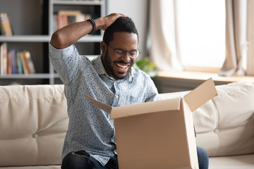 Happy african male customer hold cardboard box open post parcel
