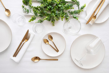 Tableware background in white gold tone.White plates,  gold cutlery,  wine glasses and decorative plant centrepiece
