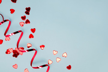 Red heart shaped confetti and ribbon on blue background with copy space.