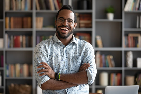 Cheerful confident african young businessman standing at home office, portrait