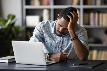 Tired bored african employee falling asleep sitting at work desk