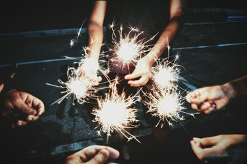 Cropped Image Of People Holding Sparklers While Standing Outdoors At Night