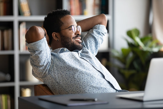 Relaxed calm african businessman resting sit at office desk