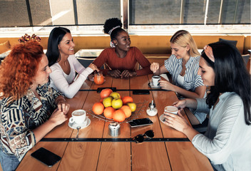 Group of young female friends having fun in cafe talking and laughing while sitting at table.