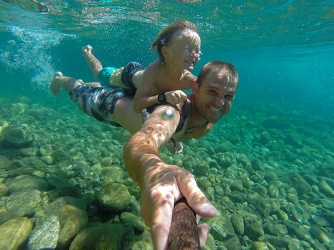 Man With His Son Swimming Underwater