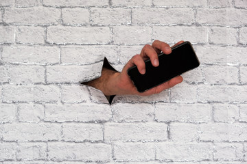hand sticking through a brick wall with a smartphone