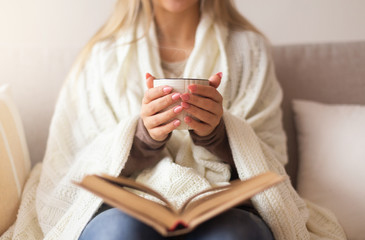 Soft photo of woman with old book and cup of coffee in hands