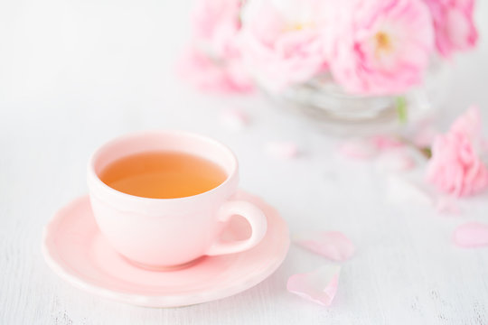Cup of tea and bouquet  of  pink  roses on rustic table.