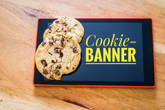 Cookies mit einem Tablet zur Verdeutlichung von Cookie Bannern für Websites mit Aufschrift Cookie-Banner