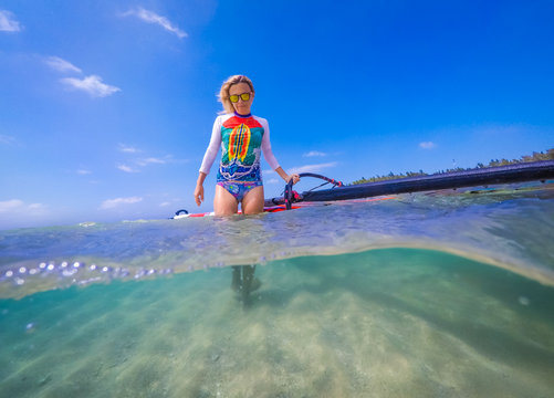 windsurfer girl with a board and a sail in tropical clear water, view from the waterline
