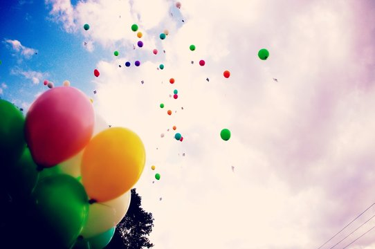 Low Angle View Of Balloons Flying Against Cloudy Sky
