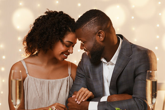 Afro couple in love cuddling at restaurant while having date