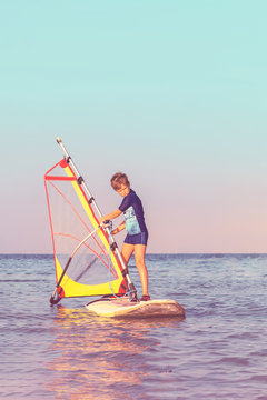 Child learning to windsurf at sunset