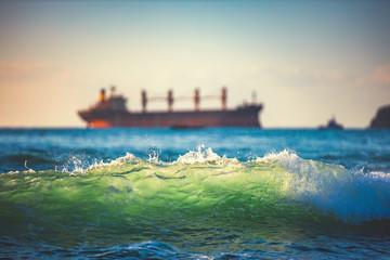 Sailing cargo ship and waves at sunrise. Transportation. Logistics. Shipping.