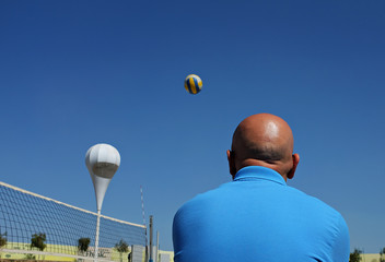 Low Angle View Of Bald Man And Ball Against Clear Sky On Sunny Day
