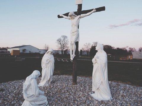 Jesus Christ Statue On Cross At Field Against Sky