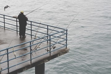 High Angle View Of Man Fishing At Santa Monica Pier Over Sea