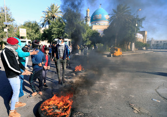 Iraqi demonstrators burn tires to block a street during ongoing anti-government protests in Baghdad