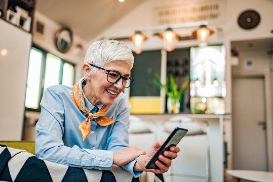 Smiling senior woman texting on smart phone, portrait, copy space.