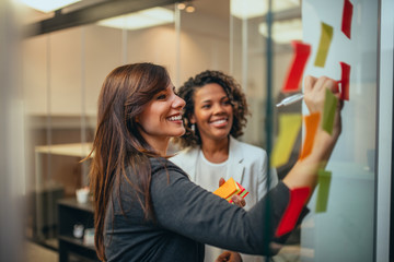 Smiling businesswoman brainstorming with adhesive notes on a glass wall in the office.