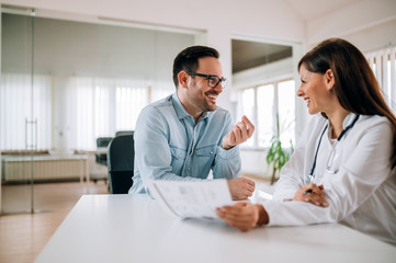 Positive handsome man talking with smiling female doctor in the office.