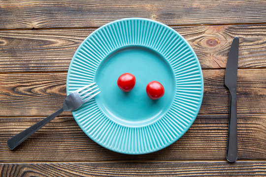 Small portion of tomatoes on turquouse plate on wooden table, top view. Diet food concept.