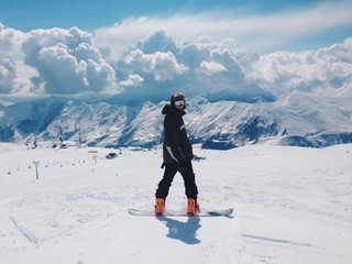 Rear View Of Snowboarder Against Snowcapped Mountains On Sunny Day