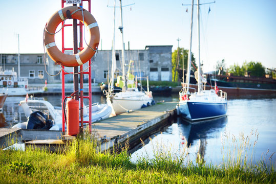 A view of a small yacht marina on a sunny summer day. Lifebuoy and fire extinguisher close-up. Port of Mersrags, Latvia