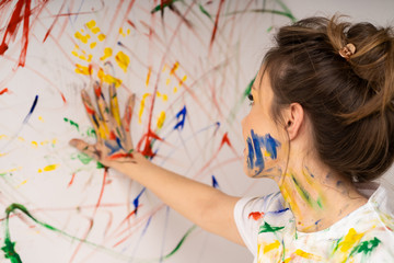 Young cheerful girl gets dirty with paint fun. Smiling woman with bright makeup and hairstyle