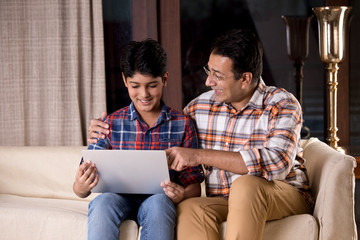Father and son astonished on receiving good news using laptop