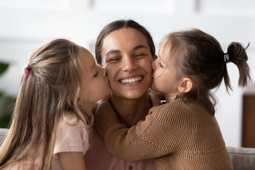 Little girl kiss on cheeks smiling young mom