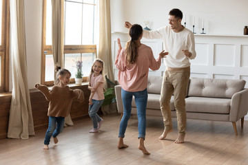 Happy family with little kids dancing in living room