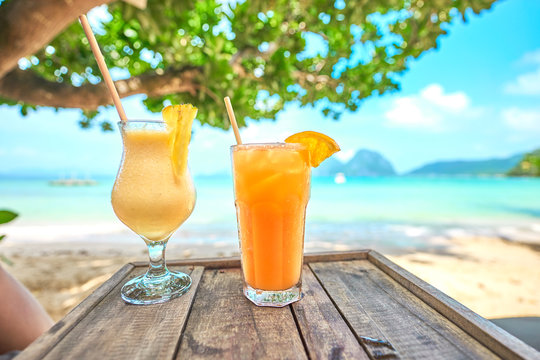 """Two cold and fruity cocktails on a wooden Table at the Beach of """"Marimegmeg"""", El Nido, Palawan, Philippines."""