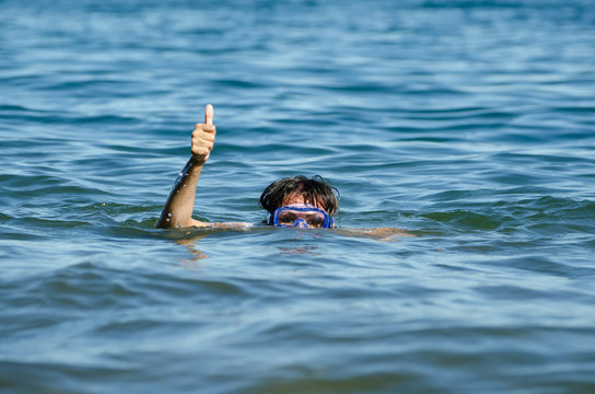 Woman Wearing Scuba Mask In Sea Showing Thumbs Up