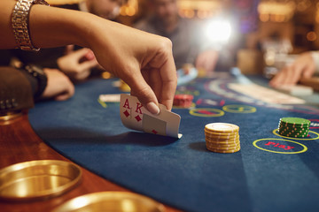 Close-up hands of a poker player checking cards in a casino.