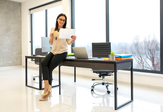 Portrait of beautiful smiling young business woman reading business reports in bright modern office with glass walls