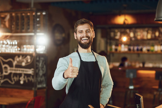 Bearded barman waiter raised his thumb up a restaurant pub bar.